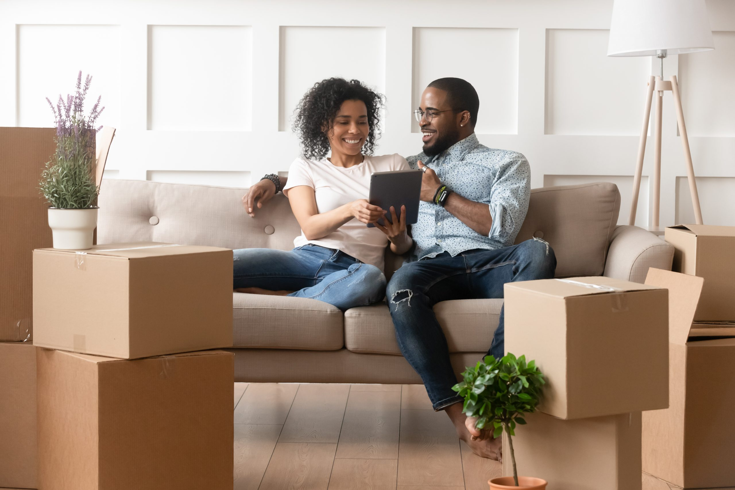 A husband and wife on a couch with moving boxes